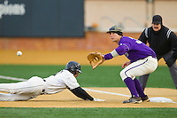 Austin Neary (33) of the Western Carolina Catamounts waits for the ball as Pat Blair (11) of the Wake Forest Demon Deacons dives back to first base at Wake Forest Baseball Park on March 26, 2013 in Winston-Salem, North Carolina.  The Demon Deacons defeated the Catamounts 3-1.  (Brian Westerholt/Four Seam Images)