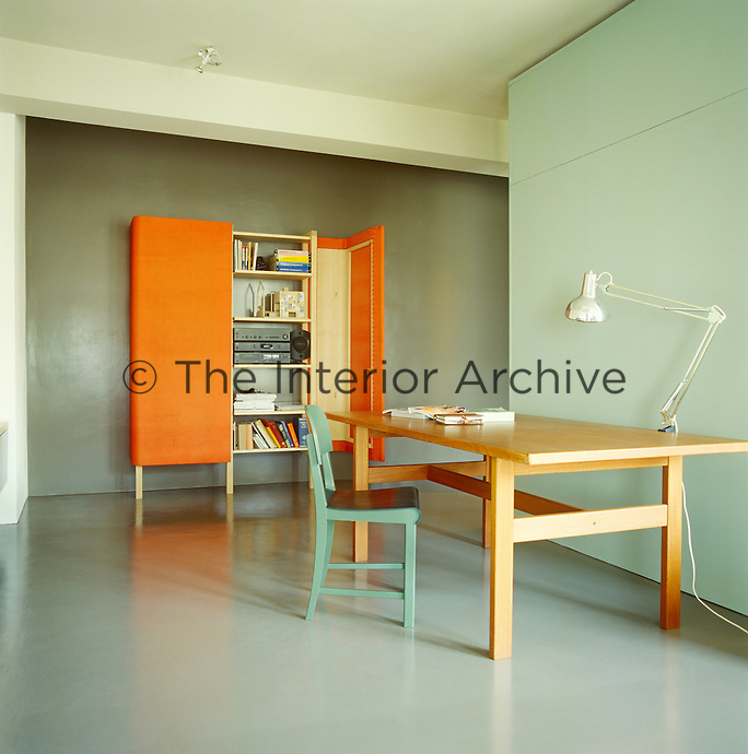 In this minimalist home office the door of a vivid orange cupboard is open to show how everyday clutter can be hidden easily from view