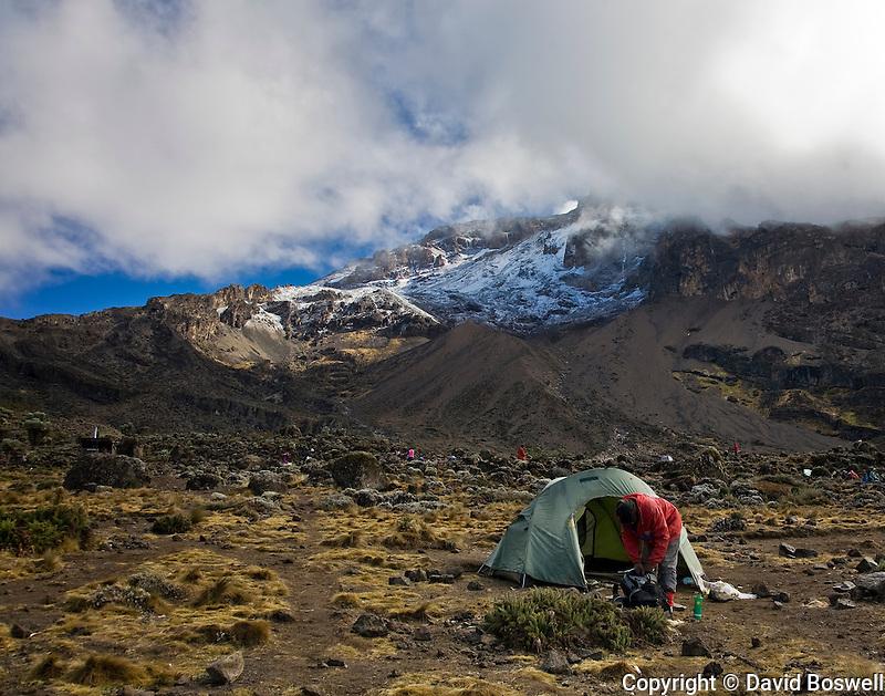 A climber on Kilimanjaro breaking camp at the third nights camp, Barranco, at 13,166 ft. (3950 m.).
