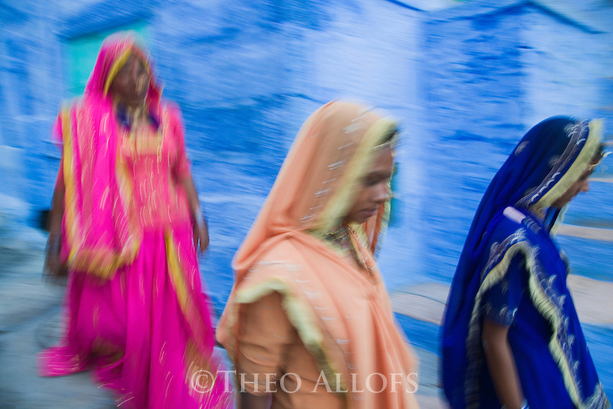 Motion Blur of Rajasthani women in colorful dresses walking through narrow street in Blue City (old town), Jodphur, Rajasthan, India --- Model Released