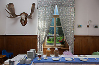 Switzerland. Canton Graubunden. Bregaglia valley. Bondo. The village was hit by two massive landslides caused by a giant rockslide swept down from Piz Cengalo on August 23, 2017. View from the window on the landslide. Dining room set up for breakfast at hotel Bregaglia. Deer antlers on the wall. A table with plates, spoons, napkins, honey, cheese and cereals (corn flakes). 26.08.2017 © 2017 Didier Ruef