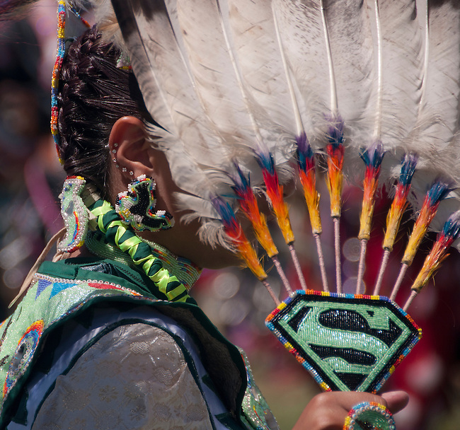 Young girl dancer with her Supergirl fan at the Julymish Pow Wow, Idaho.