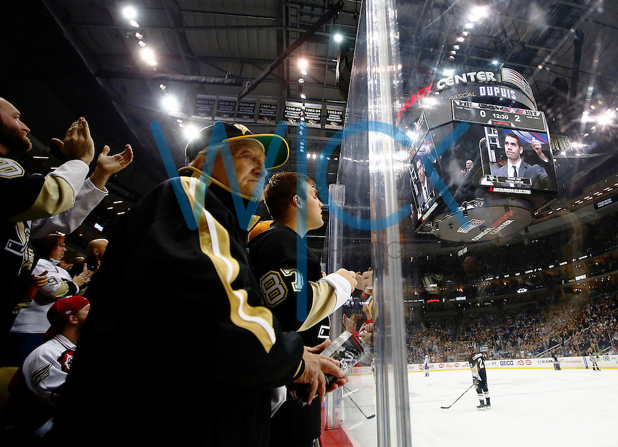 Fans look on during a tribute to Pascal Dupuis #9 of the Pittsburgh Penguins during the game against the Washington Capitals at Consol Energy Center in Pittsburgh, Pennsylvania on December 14, 2015. (Photo by Jared Wickerham / DKPS)