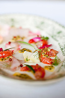 Close up of a light starter consisting of sea bass carpaccio with Sicilian shrimps marinated in a passion fruit and rose water vinaigrette and garnished with herbs and rose petals