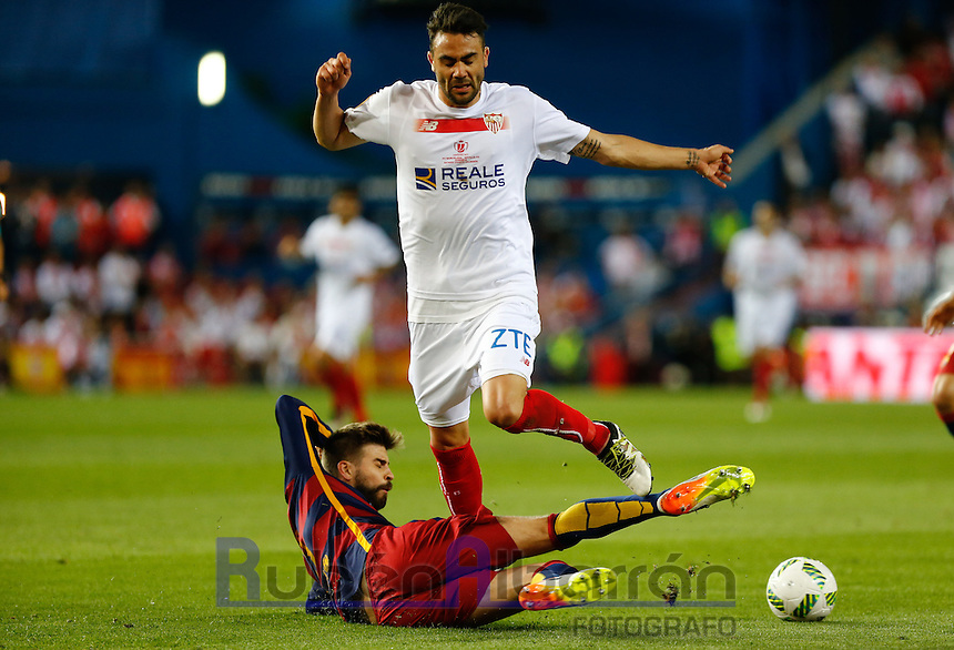 FC Barcelona´s  defense Gerard Pique and Sevilla´s midfielder  Iborra during the Final of Copa del Rey match between FC Barcelona and SevillaFC at the Vicente Calderon Stadium in Madrid, Sunday, May 22, 2016.