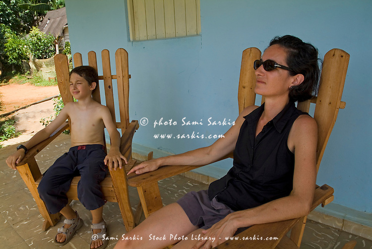 Mother and son resting on a terrace after hiking, Vinales, Pinar del Rio Province, Cuba.