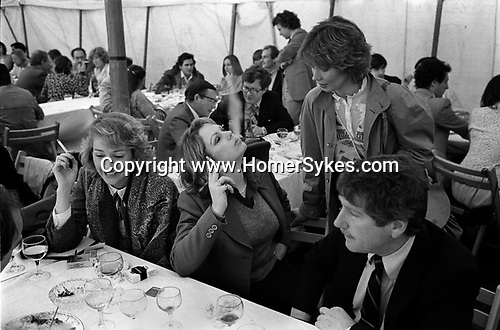 Ham Polo Ground Richmond, lunch tent women smoking at the end of the meal. Blowing a column of smoke. 1980s England