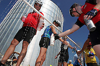 Andrew Mueller of Des Moines, right, joins other riders to fill water bottles near a large grain bin Monday morning in Laurens.