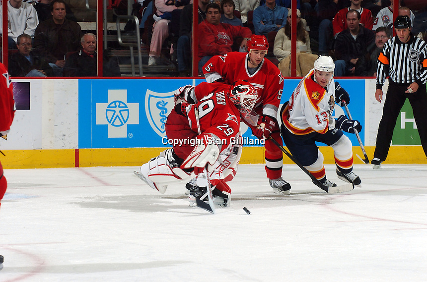 Carolina Hurricanes' goaltender Martin Gerber (29) of Switzerland attempts to clear a puck out of the zone with help from teammate Frantisek Kaberle (5) of the Czech Republic as the Florida Panthers' Juraj Kolnik of the Czech Republic closes in during their game at the RBC Center in Raleigh, NC Friday, March 3, 2006. Carolina won 5-2.
