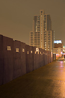 AVAILABLE FROM JEFF AS A FINE ART PRINT;<br /> <br /> AVAILABLE FROM JEFF FOR COMMERCIAL AND EDITORIAL LICENSING.<br /> <br /> Mysterious  Urban Street Scene on a Rainy Evening with Luxury Apartment Building, Wooden Fence and Sidewalk on the Far West Side of Midtown Manhattan,  New York City, New York State, USA
