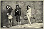 Three high School students standing on the sidewalk not paying attention to each other