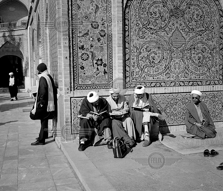 Shia students studying religous texts inside a madrasa, the walls of which are covered in ornate tiles.