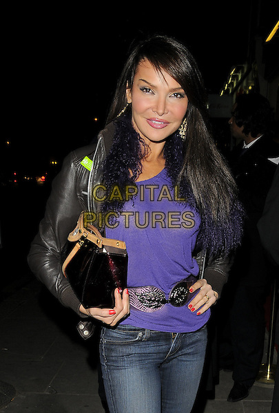 LIZZY CUNDY.The Juju new champagne & cocktail lounge launch, Juju, King's Road, London, England..December 18th, 2008.full length black leather jacket purple top jeans denim bag purse hand on hip belt.CAP/CAN.©Can Nguyen/Capital Pictures.