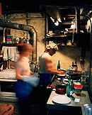 FRANCE, Val-de-Travers, a man and woman prepare food in the kitchen of Le Solait Restaurant, Jura Wine Region