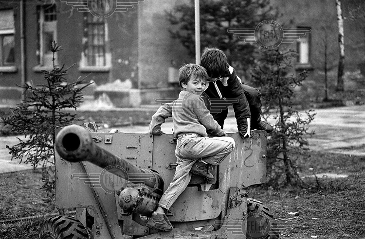 Bosnian child refugees play on an artillary piece in the Varazdin refugee camp (an old military barracks) in the winter of 1992. The boy looking at the camera is 'Elvis'. <br /> <br /> In 1992 while volunteering at the Varazdin refugee camp Panos photographer Bjoern Steinz met and became close to Elvis, a Bosnian Muslim refugee, and his family. They shared the hardships of camp life together which Steinz documented. While the prints were archived for many years two of the images always returned to Bjoern's thoughts. 25 years later he set out to try and find out what had happened to Elvis and his family in the intervening years. Modern social media made the task surprisingly easy and they were reunited in Hadzici where Elvis now lives with his family.