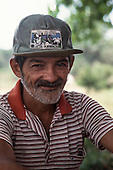 "Xapuri, Acre State, Brazil. Portrait of a bearded rubber tapper wearing a hat with ""Rio Branco, Capital of Rubber"" on the badge."