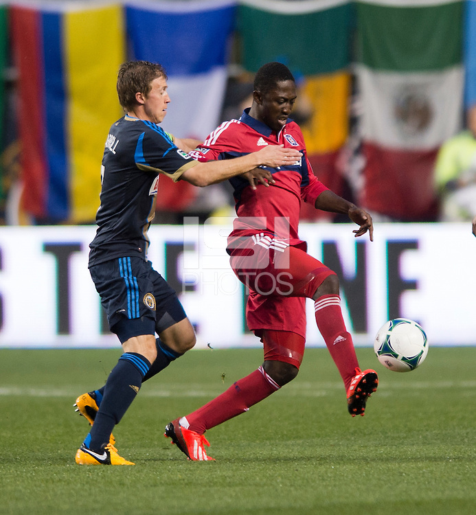 Patrick Nyarko (14) of the Chicago Fire holds the ball away from Brian Carroll (7) of the Philadelphia Union during a Major League Soccer match at PPL Park in Chester, PA.  Philadelphia defeated Chicago, 1-0.