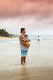 USA, Oahu, Hawaii, father and son watch the waves and surfers at Pipeline Beach on the North Shore