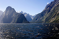 The late afternoon sun reflects off the deep waters of Milford Sound, South Island, and illuminates the snow on some of the surrounding peaks.