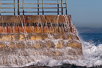 Water cascades over a brick sea wall at La Jolla Children's Pool on a gorgeous sunny winter day.  A wave has just hit the wall, and white foamy drops  are dripping and streaming off the bricks, as the water foams to the side and front of the wall.  The water and sky, though, are perfectly calm, making a great contrast.