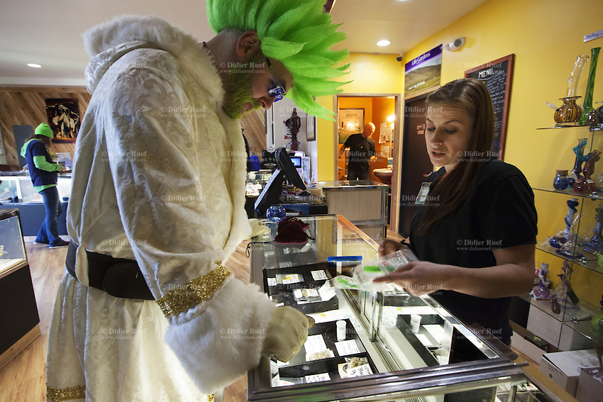 USA. Washington state. Seattle. Canna Santa at  Cannabis City. Canna Santa is the jolly green counterpart to the traditional Santa Claus with red coat, also known as Saint Nicholas, Father Christmas or Santa. Customers buying cannabis and employees selling weed in the recreational marijuana section at  Cannabis City. The staff person advices Canna Santa on various cannabis products. Cannabis City is authorized, according to cannabis legalization in Washington State, to sell marijuana as a retail store front. Cannabis City was the first state-licensed store for recreational marijuana open in July 2014. Cannabis, commonly known as marijuana, is a preparation of the Cannabis plant intended for use as a psychoactive drug and as medicine. Pharmacologically, the principal psychoactive constituent of cannabis is tetrahydrocannabinol (THC); it is one of 483 known compounds in the plant, including at least 84 other cannabinoids, such as cannabidiol (CBD), cannabinol (CBN), tetrahydrocannabivarin (THCV), and cannabigerol (CBG). 14.12.2014 © 2014 Didier Ruef