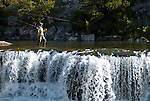 A fisherman casts to calm waters above a waterfall in northwest Wyoming.