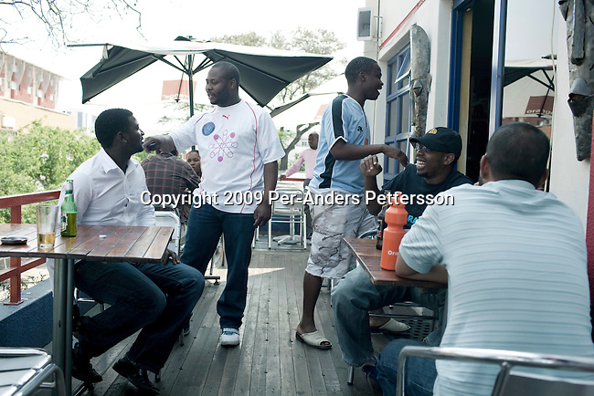 GABORONE, BOTSWANA - SEPTEMBER 22: Unidentified men socialize in a bar on September 22, 2009 in central Gaborone, Botswana. Debswana, a 50/50 partnership between the De Beers Company and the government of Botswana has brought lots of revenues to Botswana, including an impressive infrastructure such as roads and free education up to university. (Photo by Per-Anders Pettersson)....