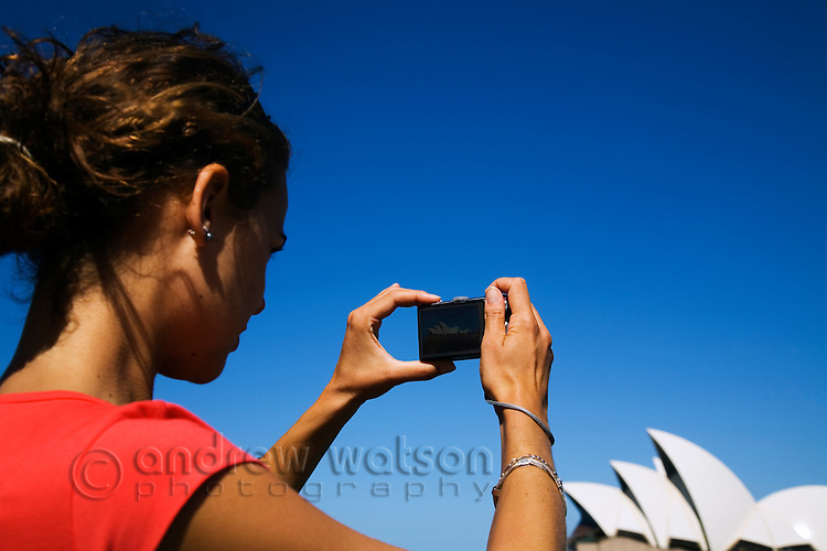 A young woman photographs the Sydney Opera House.  Sydney, New South Wales, AUSTRALIA.