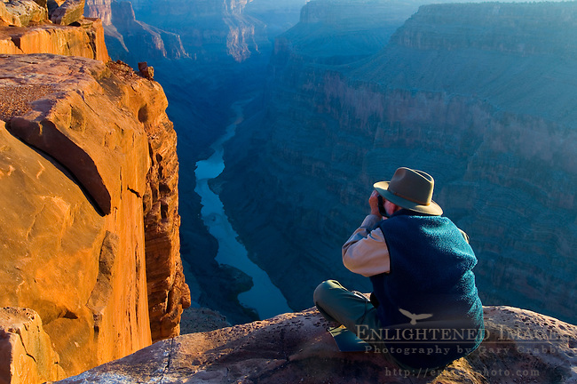 Tourist photographing the golden sunrise light on rock at the edge of a steep cliff above the Colorado River, Toroweap, Grand Canyon National Park, Arizona