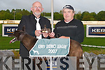 Fergies Boy with his owner Pat O'Sullivan, Dingle, who was presented with the Sherry Fitzgerald & Stephenson Crean 570 Trophy by Murt Murphy at the Denny District League Fundraiser night at Kingdom Greyhound Stadium, Tralee, on Saturday..
