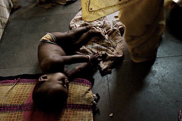 A young sex worker lies her baby on the floor as she prepares to go out onto Hanuman Galli to wait for clients.