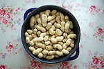 Peanuts in shells in blue bowl on floral tablecloth