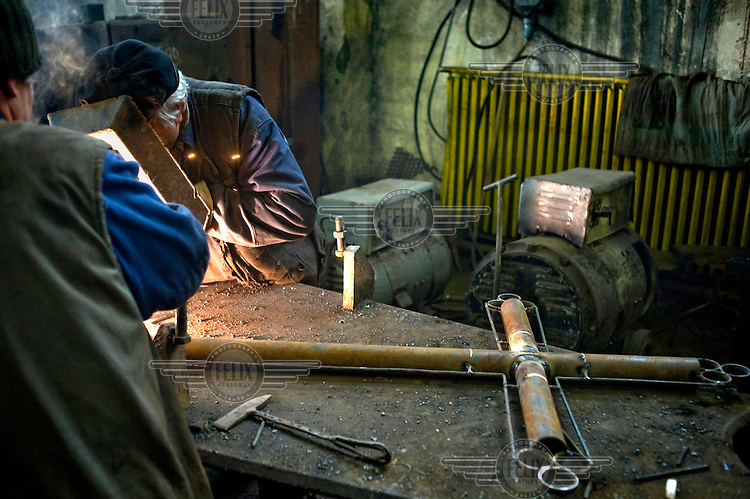 Two metal workers make some extra money by constructing an iron crucifix in the mine's workshops.
