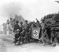 Lined up in front of a wrecked German tank and displaying a captured swastika, is group of Yank infantrymen who were left behind to &quot;mop-up&quot; in Chambois, France, last stronghold of the Nazis in the Falaise Gap area.  August 20, 1944. Tomko.  (Army Surgeon General)<br /> NARA FILE #:  112-SGA-44-12123<br /> WAR &amp; CONFLICT BOOK #:  1049