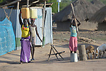 Young women carry water past a girl grinding grain in the Rhino Refugee Camp in northern Uganda. As of April 2017, the camp held almost 87,000 refugees from South Sudan, and more people were arriving daily. About 1.8 million people have fled South Sudan since civil war broke out there at the end of 2013. About 900,000 have sought refuge in Uganda.