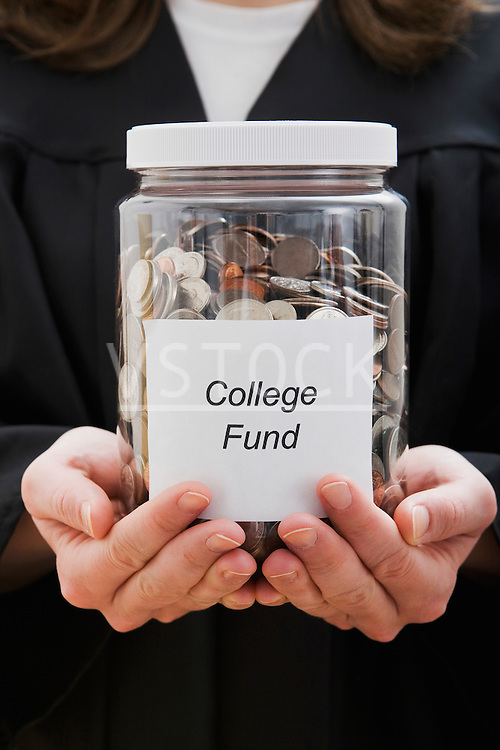 Graduate student holding college fund in jar, mid section