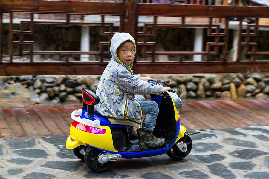 Zhaoxing, Guizhou, China, a Dong Minority Village.  Young Boy Riding a Three-wheeled Scooter.