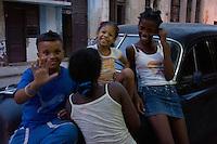kids resting and joking on a oldtimer, street scene in Havana, Cuba