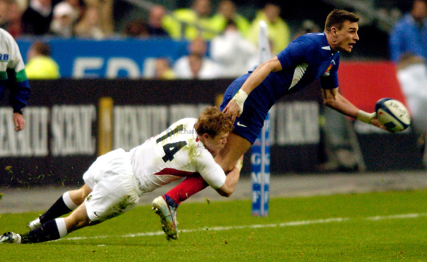 Photo: Richard Lane..France v England. RBS Six Nations. 27/03/2004..Nicolas Brusque looks for support as Josh Lewsey tackles.