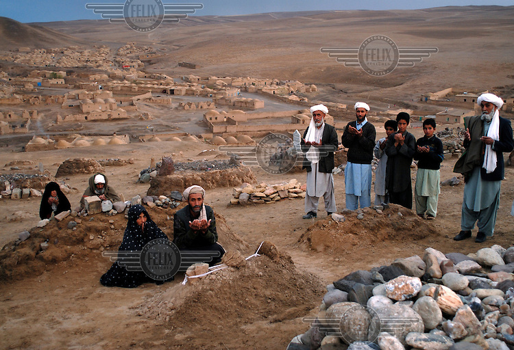 Attalullah and Rabia pray, with other villagers, at the graves of their dead babies in the Syakamarak village cemetery.