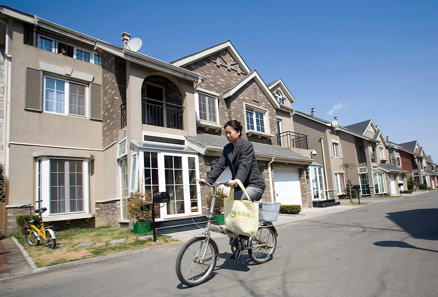 """A Chinese woman cycles though """"Lane Bridge,""""a housing develpment in northern Beijing. Suburbia is no longer an American phenomenon, a settlement pattern spreading across vast metropolitan areas. Head-spinning growth in China, Korea, India and other nations is turning the USA into a suburban laboratory for planners from these countries..."""