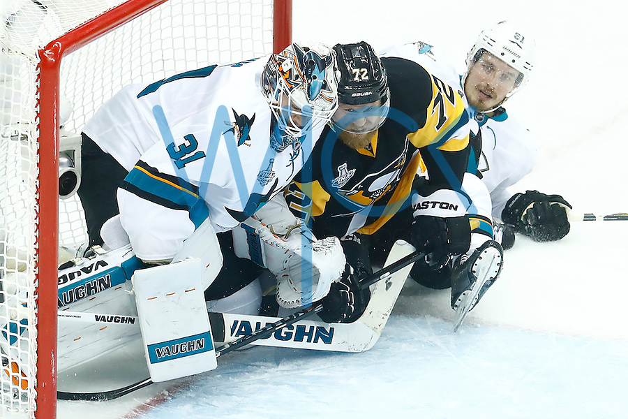 Patric Hornqvist #72 of the Pittsburgh Penguins takes a shot on Martin Jones #31 of the San Jose Sharks while being hit by Justin Braun #61 of the San Jose Sharks in the second period during game five of the Stanley Cup Final at Consol Energy Center in Pittsburgh, Pennsylvania on June 9, 2016. (Photo by Jared Wickerham / DKPS)