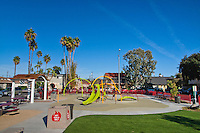 An overview of Circle Park, a pocket park located on Park Circle Drive in Anaheim, California.  This is a relatively wide-angle view of the park that places the park in the context of its surrounding parking and apartments.  Visible are play structures, an artificial-turf lawn, a picnic / BBQ area, benches, a red fence, and more.
