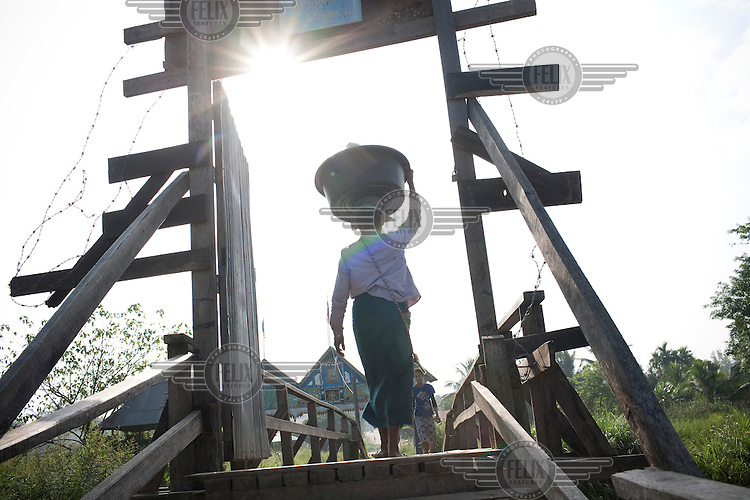 In the border village of Wale, a woman crosses over a small wooden bridge into Burma. This is one of the smallest of the border crossings. Burmese refugees had begun to return home after less than three days in Thailand. An estimated 20,000 had fled into Thailand to escape clashes in the border towns of Myawaddy and Pyaduangsu, only a day after a Burmese election which critics described as a sham..Ethnic minorities along the Thai-Burma border had warned earlier that the junta would launch a major offensive after the election, as many armed rebel groups had refused to become part of the government-controlled Border Guard Forces.