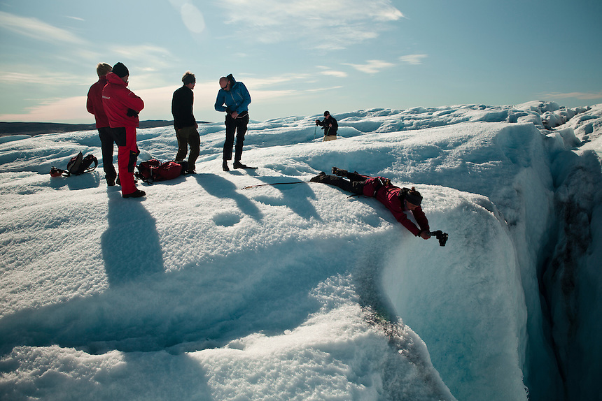 A photographer, secured by climbing equipment, attempts to photograph a 'mouline' on the Ice Cap, West Greenland, August 2011. Moulines act like drains in the ice cap, where streams of melt water have melted open a crevasse all the way to the bedrock hundreds of meters below. Photo: Ed Giles.