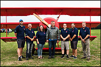BNPS.co.uk (01202 558833)<br /> Pic: RobHenry/BNPS<br /> <br /> Peter with some of the friends and family that helped him along the way.<br /> <br /> The feared Fokker Dreidecker of the Red Baron has finally flown over Britian skies - after British based German doctor 'Baron' Peter von Brueggemann spent 9 years building a replica in his garage.<br /> <br /> The German GP based in Norfolk has spent 9 years building a Fokker triplane as a tribute to infamous WW1 Ace Manfred von Ricthofen, who terrorised the skies over the Western front during the first war.<br /> <br /> Dr Peter Brueggemann, 53, fufilled his childhood dream and emulated the notorious German fighter Ace when his hand built Dreidecker finally took off this week.<br /> <br /> Dr Brueggemann has even acquired the title Baron from the independent territory of Sealand so he can take to the skies as Baron Peter von Brueggemann in homage to his idol.<br /> <br /> The GP at the Holt Medical Practice in Norfolk finally reached for the sky at Felthorpe airfield near Norwich this week in front of nervous friends and family after thousands of hours spent crafting the aircraft.<br /> <br /> The father-of-two, who has lived in England with wife Sue for 20 years, has been taking flying lessons since his project began.