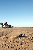 USA, Los Angeles, a woman and her daughter sitting in the sand on the beach off the Venice Boardwalk