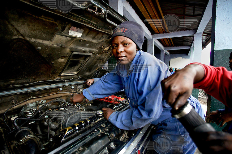 Young women learning vehicle mechanics and other practical skills in a school workshop.
