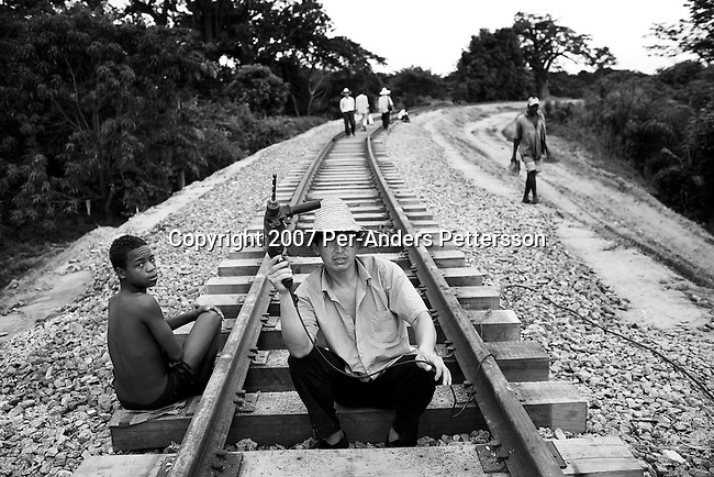 DONDO, ANGOLA APRIL 4: An unidentified Chinese railway worker drills holes on the newly put tracks on April 4, 2007 in Dondo, about 200 kilometers outside Luanda, Angola. Chinese companies are building and upgrading two different railways in Angola, and this part is about 500 kilometers long. All the special equipment has been shipped from China and hundreds of workers live in military style road camps. They are moved as the tracks are laid down. Tens of thousands of Chinese has come to Africa the last years to work in infrastructure projects and businesses. Chinese companies are often the lowest bidders for contracts, pricing out the more expensive European companies. The Chinese people often live where they work and rarely interact with the local population. Most Chinese don't speak English and they are mostly staying in the compounds cooking their Chinese food. (Photo by Per-Anders Pettersson)..