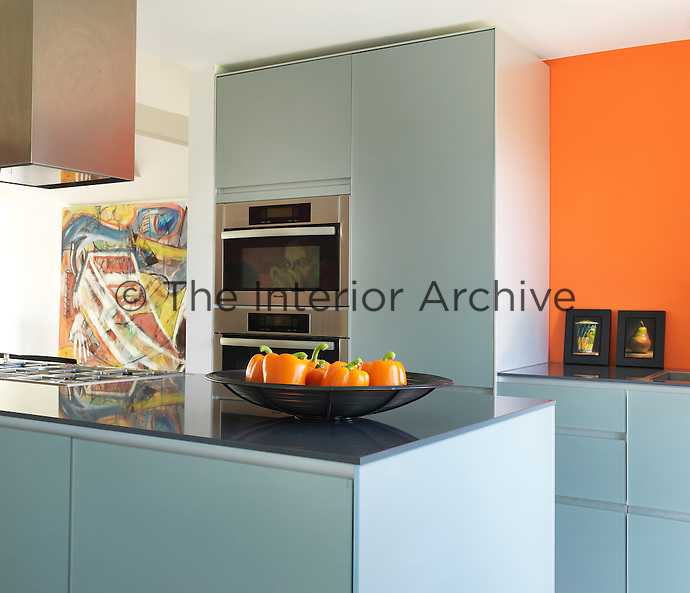The open-plan contemporary kitchen has a central island complete with hob